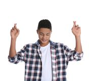 African-American teenage boy crossing his fingers on white stock image