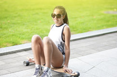 African American Teenage Girl with Dreadlocks Posing on Longboard Skate Outdoors Royalty Free Stock Photos