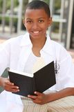 African American Teenager Boy Reading a Book Stock Photos