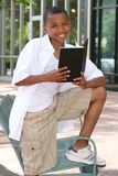 African American Teenager Boy Reading a Book. On a bench outdoors, city street Royalty Free Stock Images
