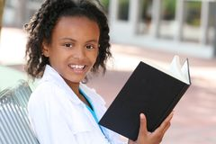 African American Teenager Girl Reading a Book. On a bench outdoors, city street Stock Photography