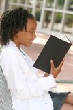 African American Teenager Girl Reading a Book. On a bench outdoors, city street Stock Photos