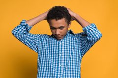African American teenager holds on to head. royalty free stock image