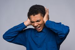 African American teenager screams in anger, covering ears. stock image