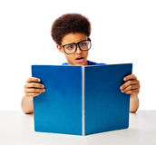 African American teenager shocked reading. Funny, surprised African American teenager, school boy with glasses reading book with shock Stock Photography