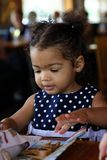 African-American Toddler female. African-American toddler girl in a restaurant, playing with her coloring menu with a waitress in the background Royalty Free Stock Images
