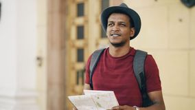 African american tourist man looking into paper city map exploring sightseeings during travelling in Europe. An country Stock Photos