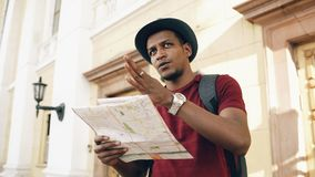 African american tourist man looking into paper city map exploring sightseeings during travelling in Europe Royalty Free Stock Photo