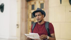 African american tourist man looking into paper city map exploring sightseeings during travelling in Europe. An country Stock Photo