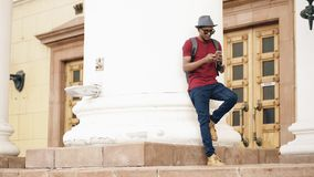 African american tourist man surfing online social media with smartphone while travelling in Europe. Mixed race tourist man surfing online social media with Stock Photos