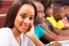 African american university student. Beautiful female african american university student in lecture hall with classmates Royalty Free Stock Photo