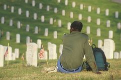 African-American Veteran Sitting in Cemetery Stock Photo