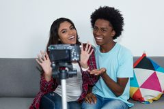 African american vlogger and influencer girl recording video blog. With camera at home stock image