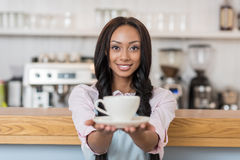 African american waitress in apron holding coffee cup and looking at camera at cafe. Attractive african american waitress in apron holding coffee cup and looking Royalty Free Stock Photos