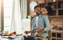 African-american wife kissing husband in kitchen. Family preparing dinner together stock photos