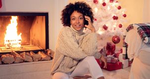 Woman by fireplace and white christmas tree. African American Woman with afro haircut sitting by fireplace and white christmas tree covered in red ornaments and Royalty Free Stock Image