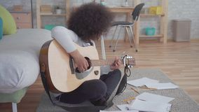African american woman with an afro hairstyle composes a song and plays the guitar sitting on the floor. At home stock footage