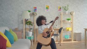 African american woman with an afro hairstyle expressive playing on the guitar. Beautiful african american woman with an afro hairstyle expressive playing on the stock footage