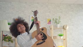 African american woman with an afro hairstyle expressive playing on the guitar slow mo. Beautiful african american woman with an afro hairstyle expressive stock video footage