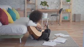 African american woman with an afro hairstyle plays guitar sitting on the floor. In a modern apartment stock video footage