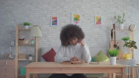 African american woman with an afro hairstyle reading a book at the table. In a modern apartment stock footage