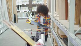 African american woman with an afro hairstyle the store chooses repair tools. African american woman with an afro hairstyle in shirt and glasses the store stock video