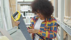African american woman with an afro hairstyle in the store chooses a saw for repair. African american woman with an afro hairstyle in shirt and glasses in the stock footage