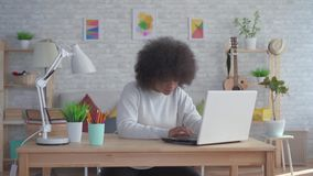 African american woman with an afro hairstyle uses a laptop at home. Beautiful african american woman with an afro hairstyle uses a laptop at home stock footage