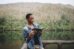 African American woman alone in nature reading a book leisure concept Stock Image