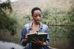 African American woman alone in nature reading a book leisure concept Stock Photos