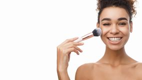 African-american woman applying blush on face with brush tool stock photo