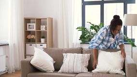 African american woman arranging sofa cushions stock footage