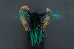 African American Woman with Beautiful Teal Green Blue Braids. In hair tossing hair in action shot on dark background stock image