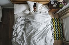 African American woman on bed insomnia and noise pollution concept Royalty Free Stock Images