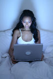 African American woman in bed with laptop Royalty Free Stock Photos