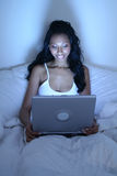 African American woman in bed with laptop Stock Photography