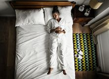 African American woman on bed sleeping alone Royalty Free Stock Photography