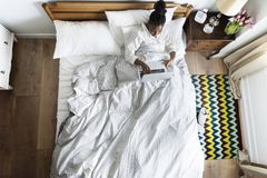 African American woman on bed using a laptop Royalty Free Stock Photography