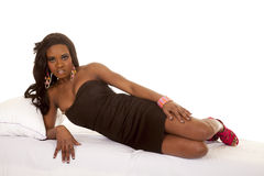 African American woman black dress lay side serious. An African American woman laying on her bed in her black dress Royalty Free Stock Images