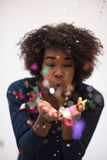 African American woman blowing confetti in the air. Beautiful young black woman celebrating new year and chrismas party while blowing confetti decorations to Stock Image