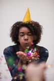 African American woman blowing confetti in the air. Beautiful young black woman celebrating new year and chrismas party while blowing confetti decorations to Royalty Free Stock Photos