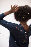 African American woman blowing confetti in the air. Beautiful young black woman celebrating new year and chrismas party while blowing confetti decorations to Royalty Free Stock Images