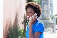 African american woman in a blue shirt speaking at phone Stock Photos