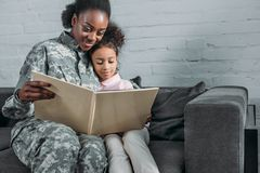 African american woman in camouflage clothes and child. Reading book stock photo