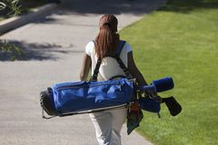 African American Woman Carrying Golf Bag Royalty Free Stock Photos