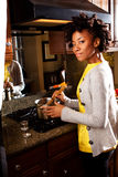 African American woman cooking in the kitchen. Happy African American woman cooking in the kitchen Royalty Free Stock Photos
