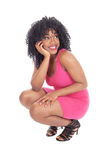 African American woman crouching. A young pretty African American woman in a pink dress and curly black Stock Images
