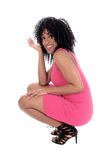 African American woman crouching. A young pretty African American woman in a pink dress and curly black Stock Photography