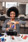African american woman with curly hair looking amused. New collection of brushes. African american woman wearing a trendy shirt looking amused while royalty free stock photography