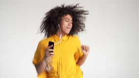 African american woman dancing while listening music on headphones stock video